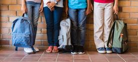 Children holding backpacks.