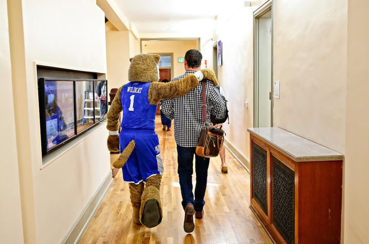 photo of wildcat and faculty member walking