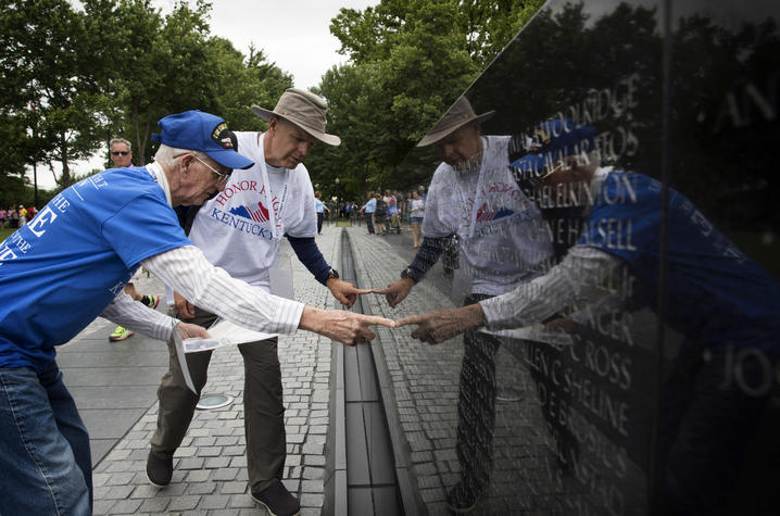 Photo of A UK Honor Flight veteran and guardian searching for names on the Vietnam Veterans Memorial.