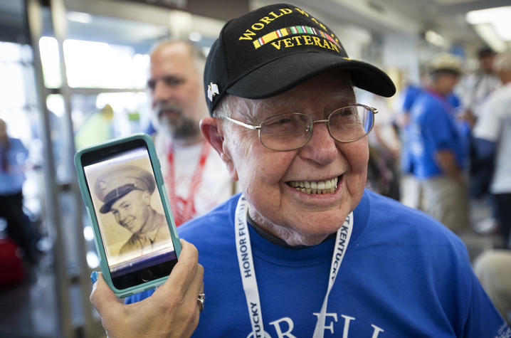 Photo of Cecil Hill, a World War II veteran, posing next to a photo of him in service.
