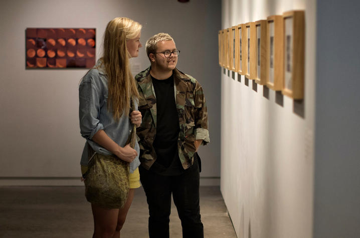 "photo of 2 students looking at David Wischer's work - ""Faculty Series: Vol. I"""