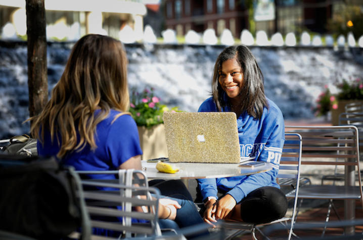 photo of two girls with laptop