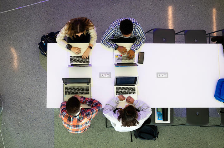 Students seated at table with laptops