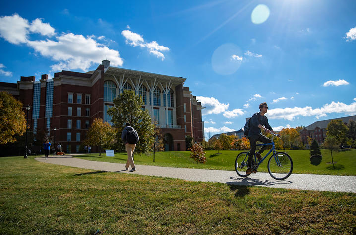 photo of student walking passing student on bike around the bowl of Young Library