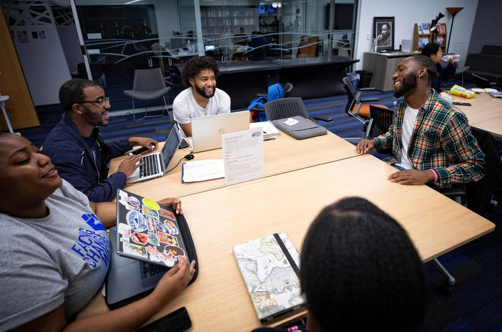 photo of 4 students seated talking with Eli Caldwell in MLK Center
