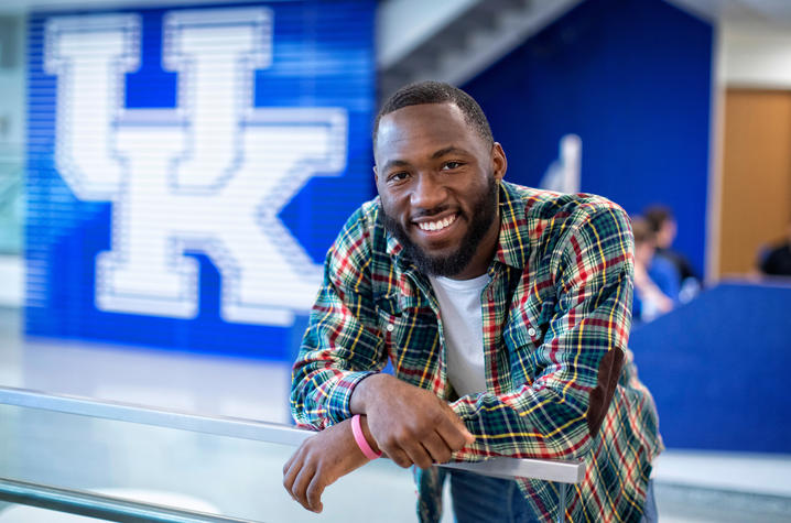 photo of Eli Caldwell leaning on glass railing in front of UK sign in student center