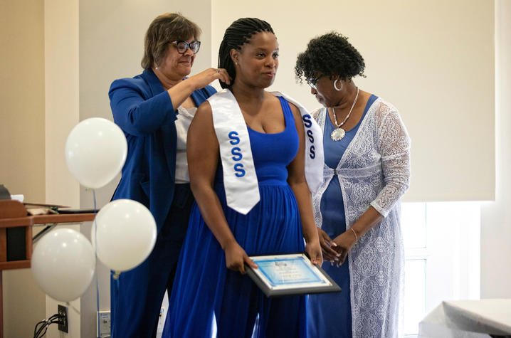 photo of 2 Student Support Services staff members presenting honors to student