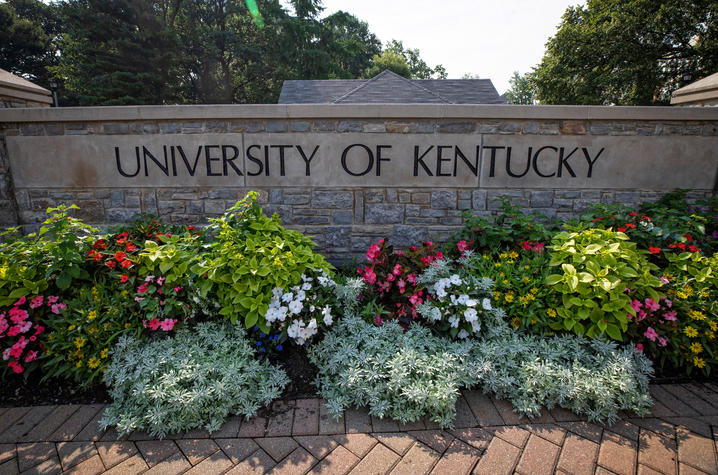 """photo of stone wall at campus entrance that says """"University of Kentucky"""" and has blooming flowers in front of it"""