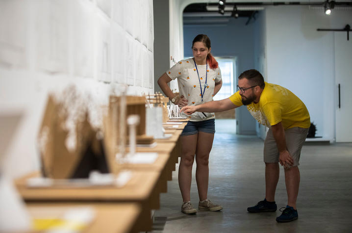 photo of 2019 GSA student and adult looking at model from Architecture + Design