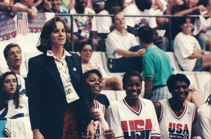 Dr. Ireland stands to the left of the screen with 3 members of the US women's basketball team sitting to her right