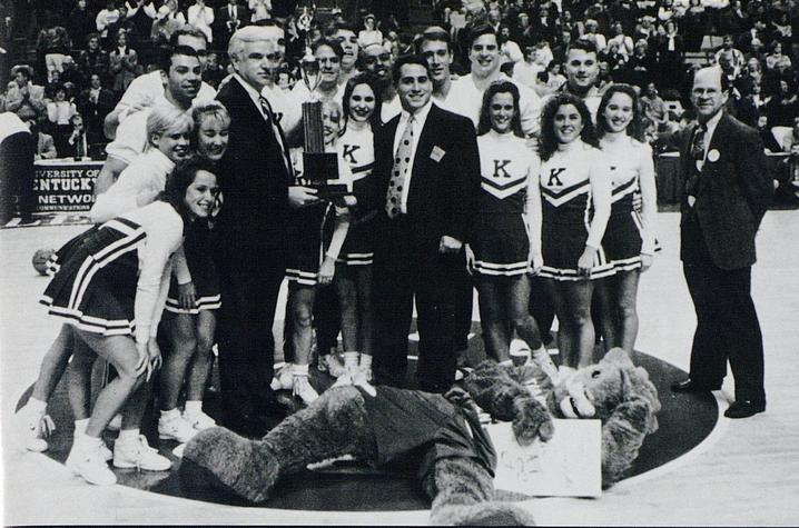black and white photo of UK Cheerleading recognized at Rupp with trophy - 1996 Kentuckian