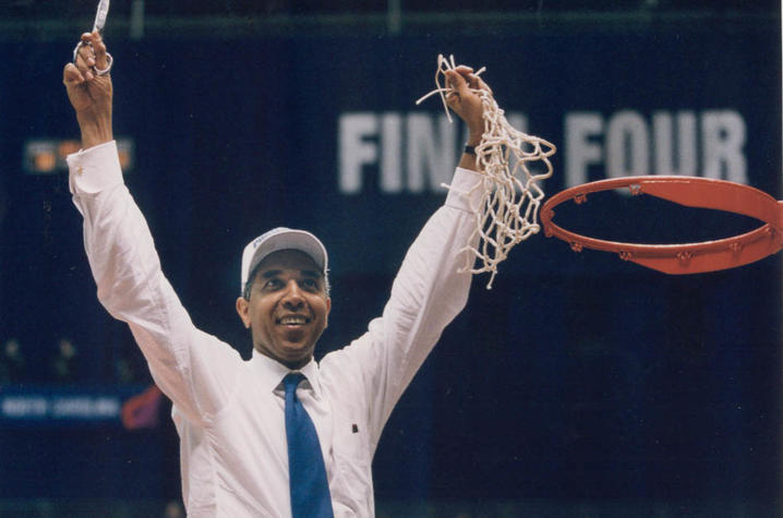 """Orlando """"Tubby"""" Smith cutting basketball net in white shirt and white hat"""