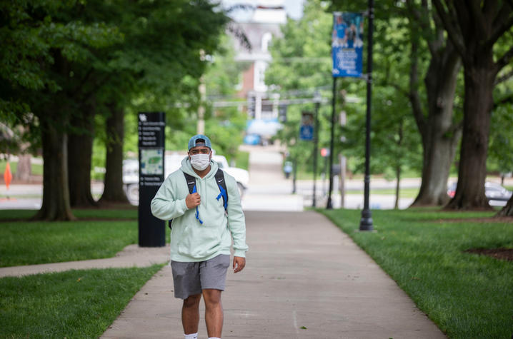 photo of student walking on campus wearing mask