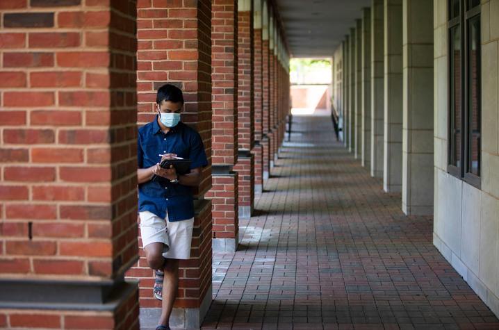 Student in mask against brick pillar