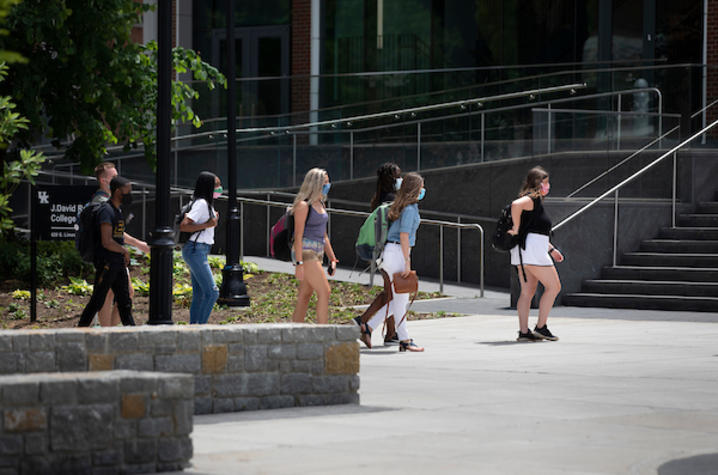 Photo of students wearing masks walking through campus