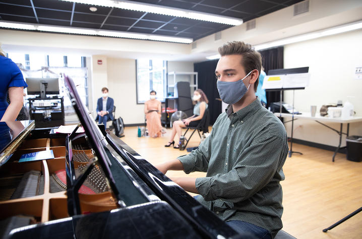 photo of masked pianist playing in Arnold class