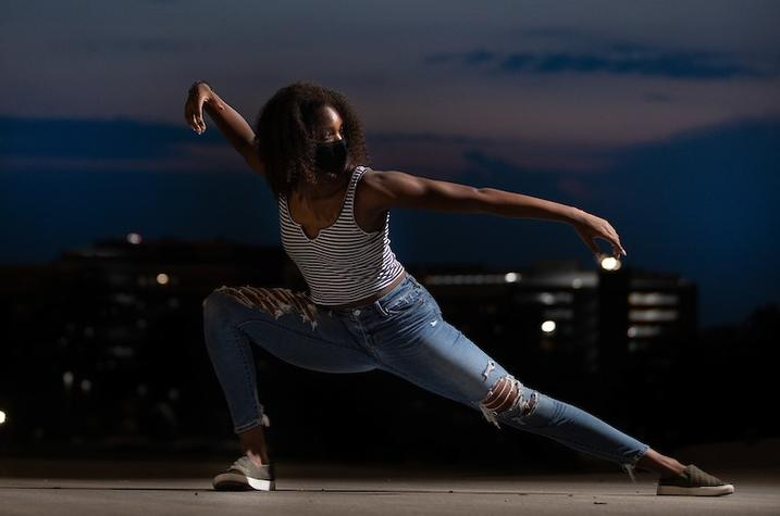 photo of UK dance student peforming with campus landscapte behind her