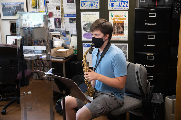 photo of masked saxophone student taking lesson in Miles Osland's office behind plexiglass