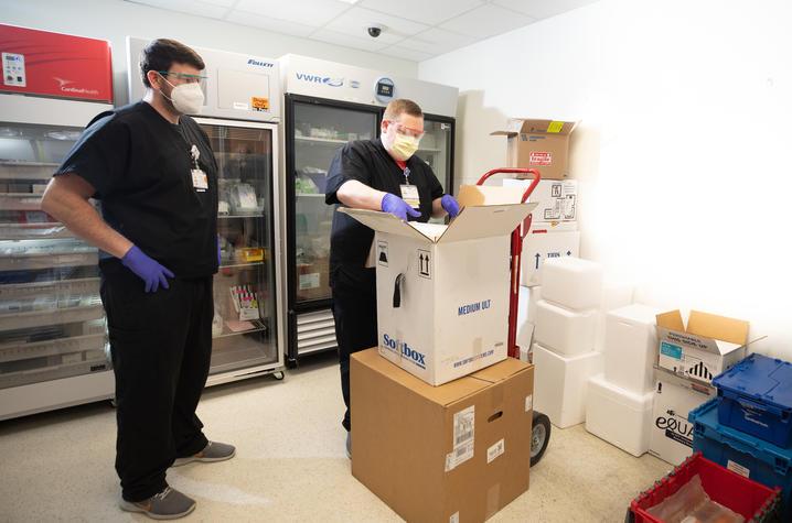 UK HealthCare Pharmacy technicians Cody Purnell and Brad Watkins with Pfizer COVID-19 vaccine mock shipment. Mark Cornelison | UK Photo