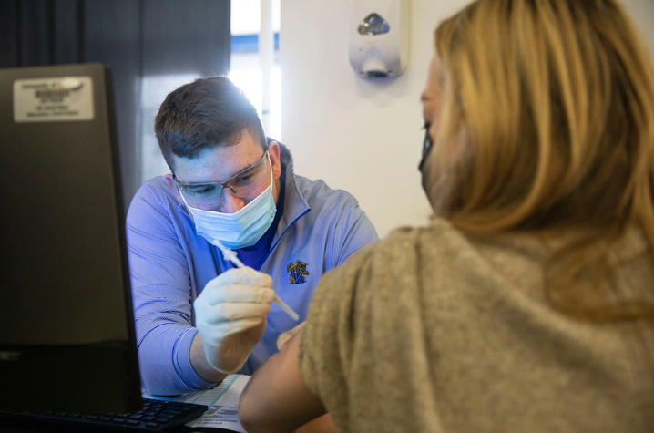 Image of Colin Goodfellow administering a COVID vaccine at the UK vaccine clinic