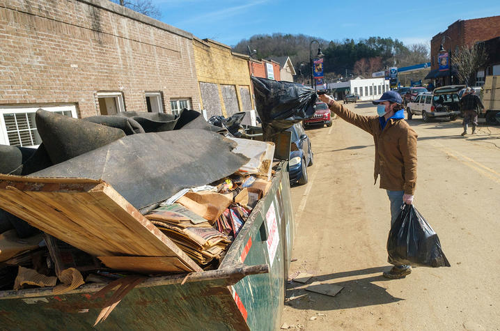 Benjamin Bayless, AGR member and a junior agricultural ecosystems sciences major from Franklin, throws trash into a dumpster in downtown Beattyville.