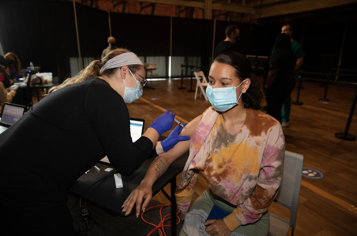 Photo of a female student getting a vaccine shot at the Blue Box Theater