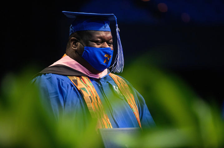 photo of masked Reginald Smith Jr. in cap and gown holding diploma at Commencement