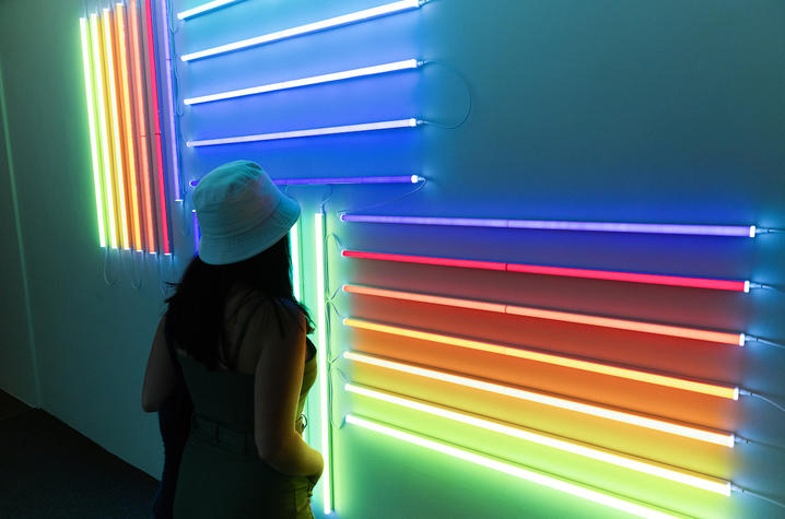 """photo of student looking at neon artwork at UK Art Museum's """"Coloring"""" exhibition"""