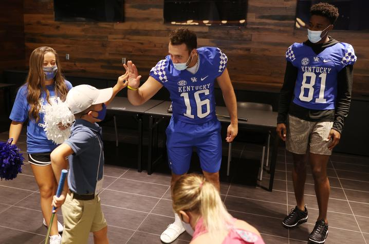 photo of football players high-fiving young golfers
