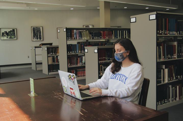 photo of masked student working on laptop in library