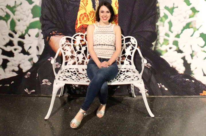 photo of Amaris Aleah Wade seated on white metal bench with mural of Frida Kahlo behind her