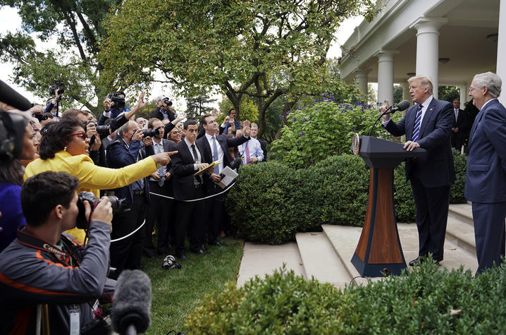 April Ryan, at left in yellow, has a question for President Donald Trump