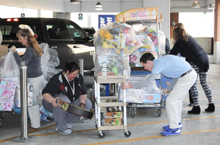 Staff from the Kentucky Children's Hospital collect the donations from the Ard family.