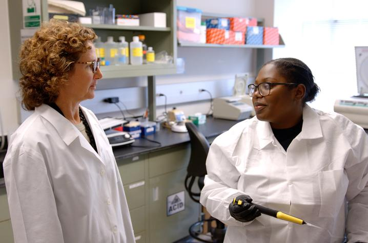 Barbara Nikolajczyk (right), an associate professor of pharmacology & nutritional sciences, talks to lab tech Maya Cleveland. Cleveland is working on her master's in medical science.