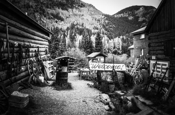 black and white Alethea Devary photo of items between to buildings with mountain scape in back