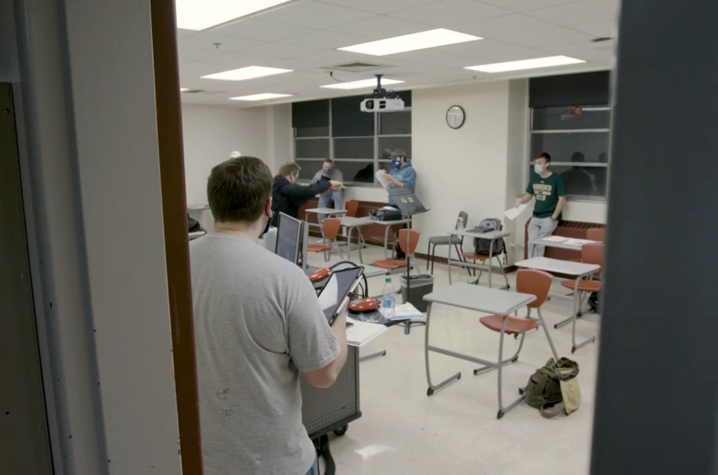 photo of masked acoUstiKats members spaced out in classroom for a rehearsal