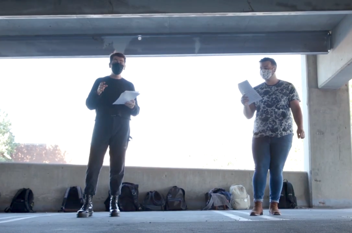 photo of 2 masked acoUstiKats rehearsing in garage structure with backpacks on ground behind them