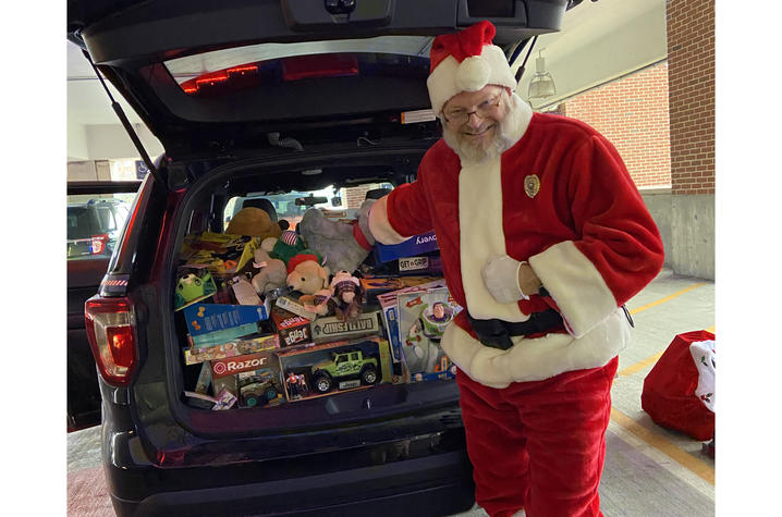 photo of UK Police Chief Joe Monroe dressed as Santa Claus in December 2019. He is standing by a vehcile packed with donated toys.