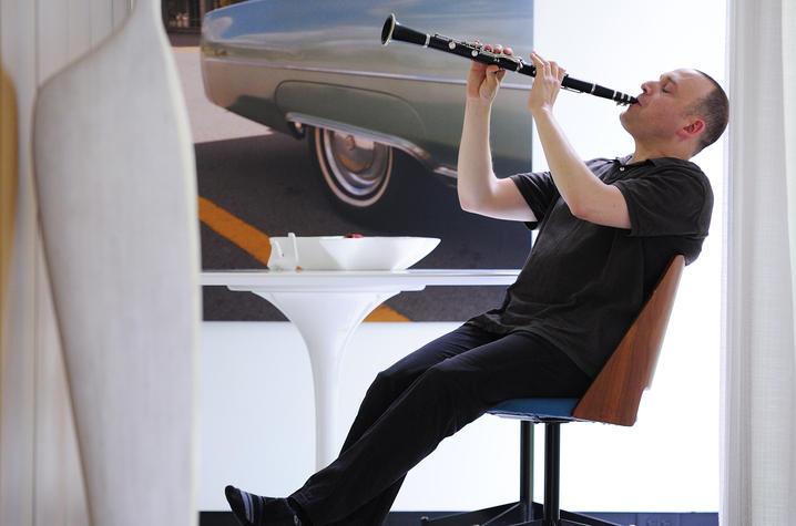photo of Derek Bermel seated playing clarinet