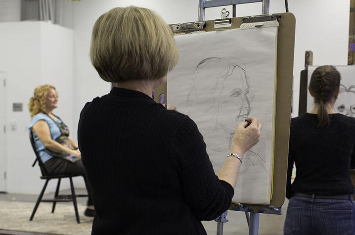 photo of students drawing instructor in Fine Arts Institute class
