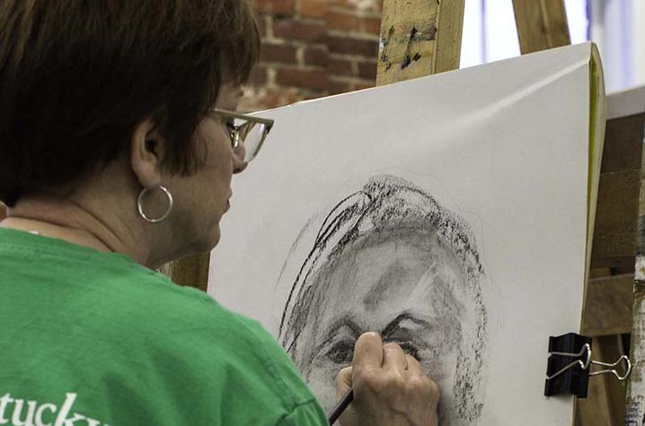 photo of student working on drawing at Fine Arts Institute