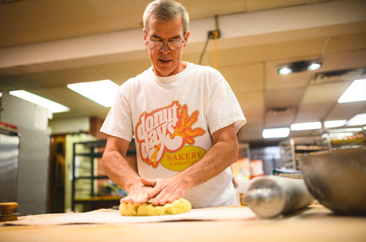 As the owner of Donut Days Bakery, Fred Wohlstein spends his days surrounded by delicious—and tempting—baked goods. (Photo was taken before COVID-19)