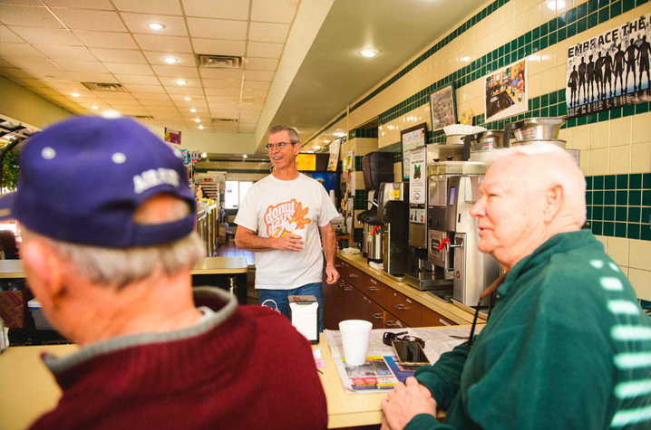 Fred Wohlstein talking with his customers inside Donut Days Bakery. (photo was taken prior to COVID-19)