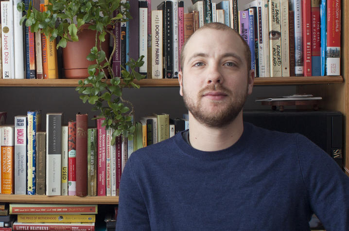 headshot photo of Garrett Hansen seated in front of shelves of books with plant
