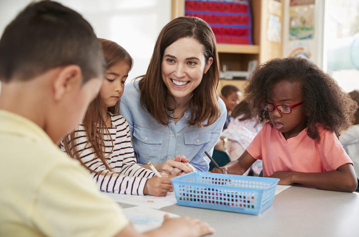photo of teacher visiting with 3 elementary school kids at table