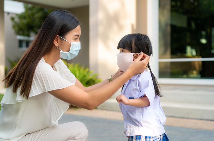 Photo of mother adjusting child's face mask