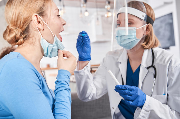 stock photo of health care professional in mask and shield swabbing young adult's mouth