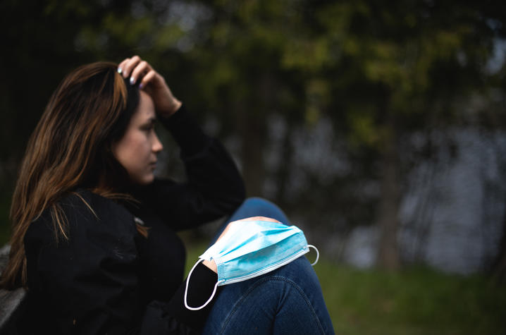 photo of young woman outside coping with stress of social isolation, face mask on knee