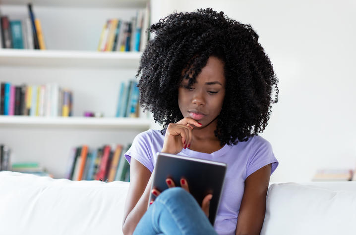 photo of African American woman sitting on couch reading newspaper online