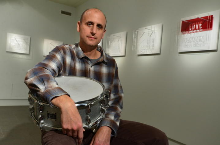 photo of Michael Gould with drum at exhibit